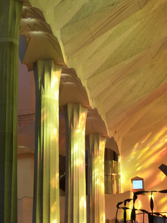 Light from the red and gold windows reflecting onto the interior pillars in the Sagrada Familia