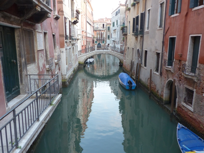 A quiet side canal with arching bridge in Venice