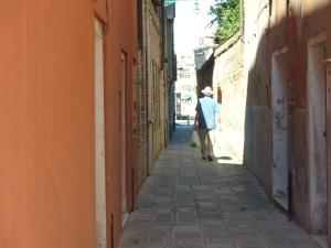 Man walking down narrow street in Venice