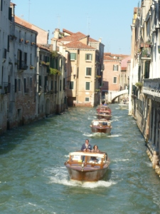 A procession of sleek wooden launches on one of Venice's canals