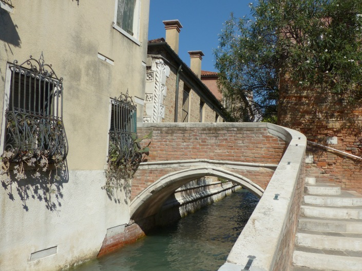 A curving bridge over a smoothly flowing canal in Venice