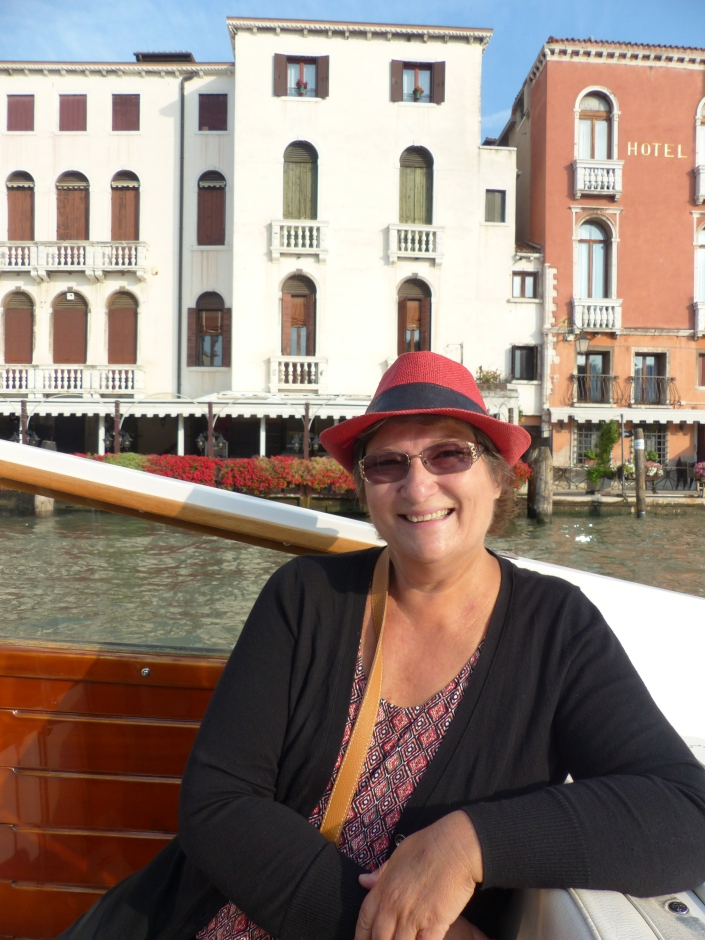 The author on a launch in Venice with buildings behind