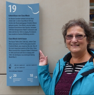 Woman standing next to a plaque showing information about the site of the birthplace of Clara Schumann (nee Wieck)